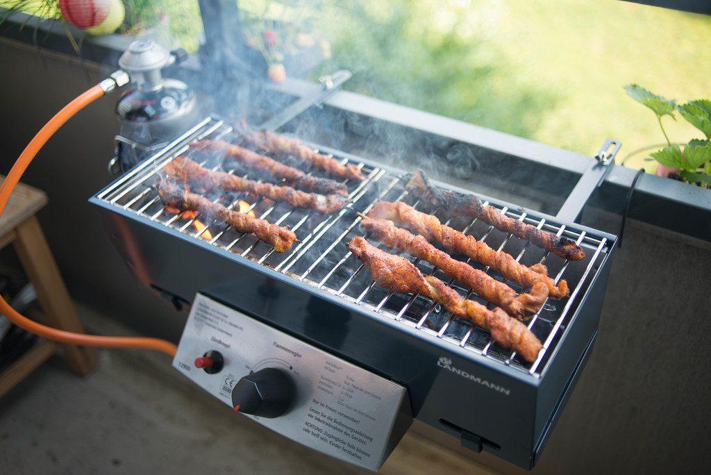 Vier de zomer op een loungekussen - balkon barbecue